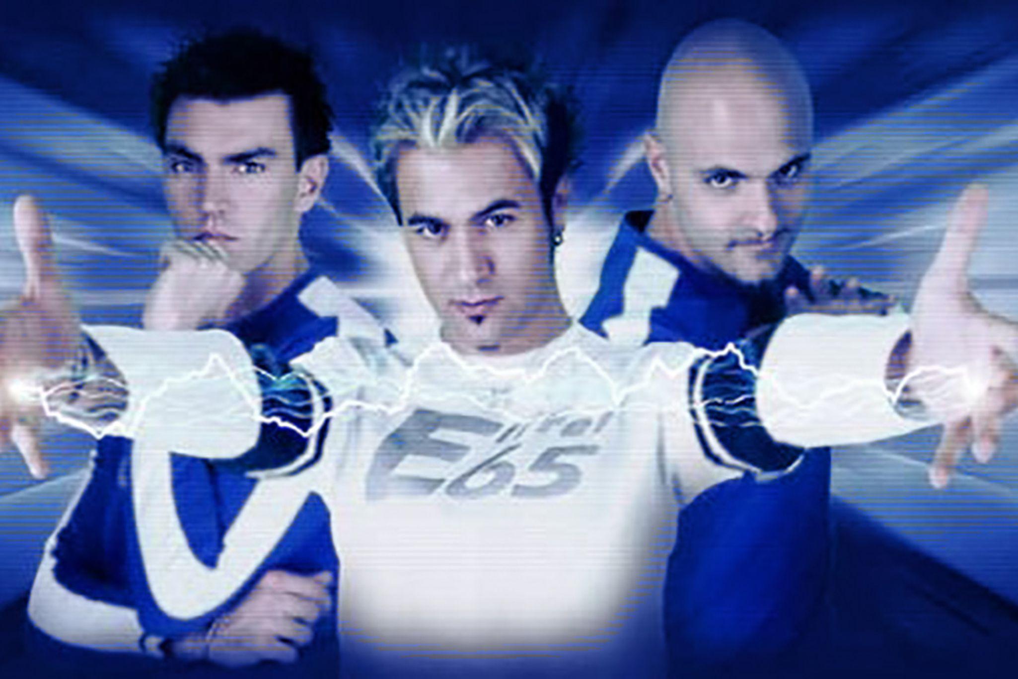 Los tres miembros de Eiffel 65 con peinados de cresta sobre un fondo futurista y luminoso